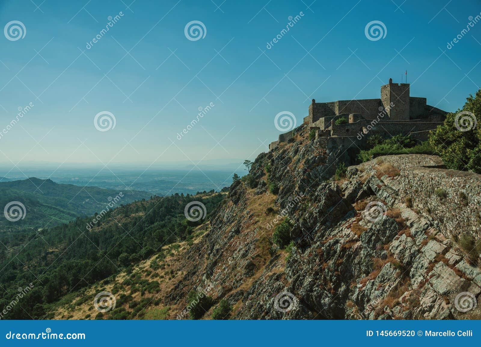 Mur en pierre et tour de château et de paysage montagneux