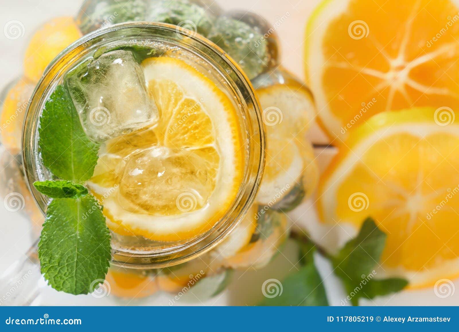 Murarekrus av en hemlagad lemonad med mintkaramellen och is, citrusskivor på en lantlig vit träbakgrund
