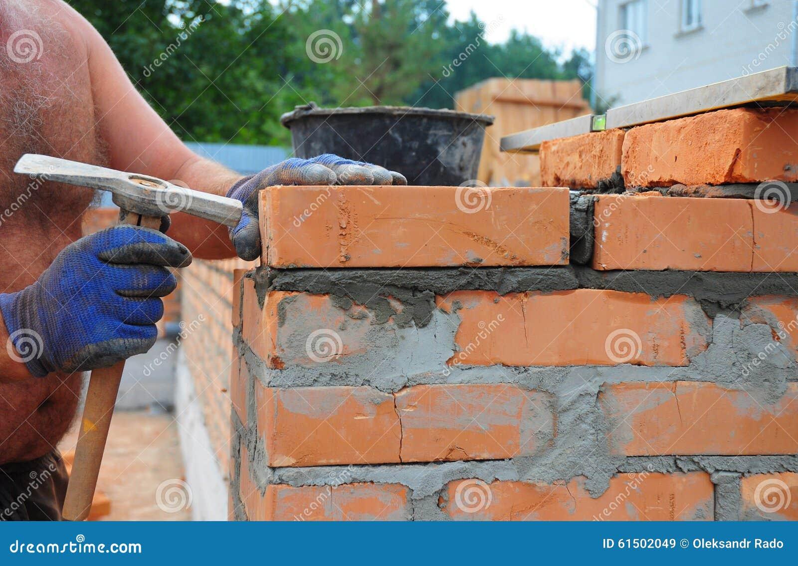 Muratore Using Un Martello Di Lavoro Di Muratura Per Costruire Nuovo