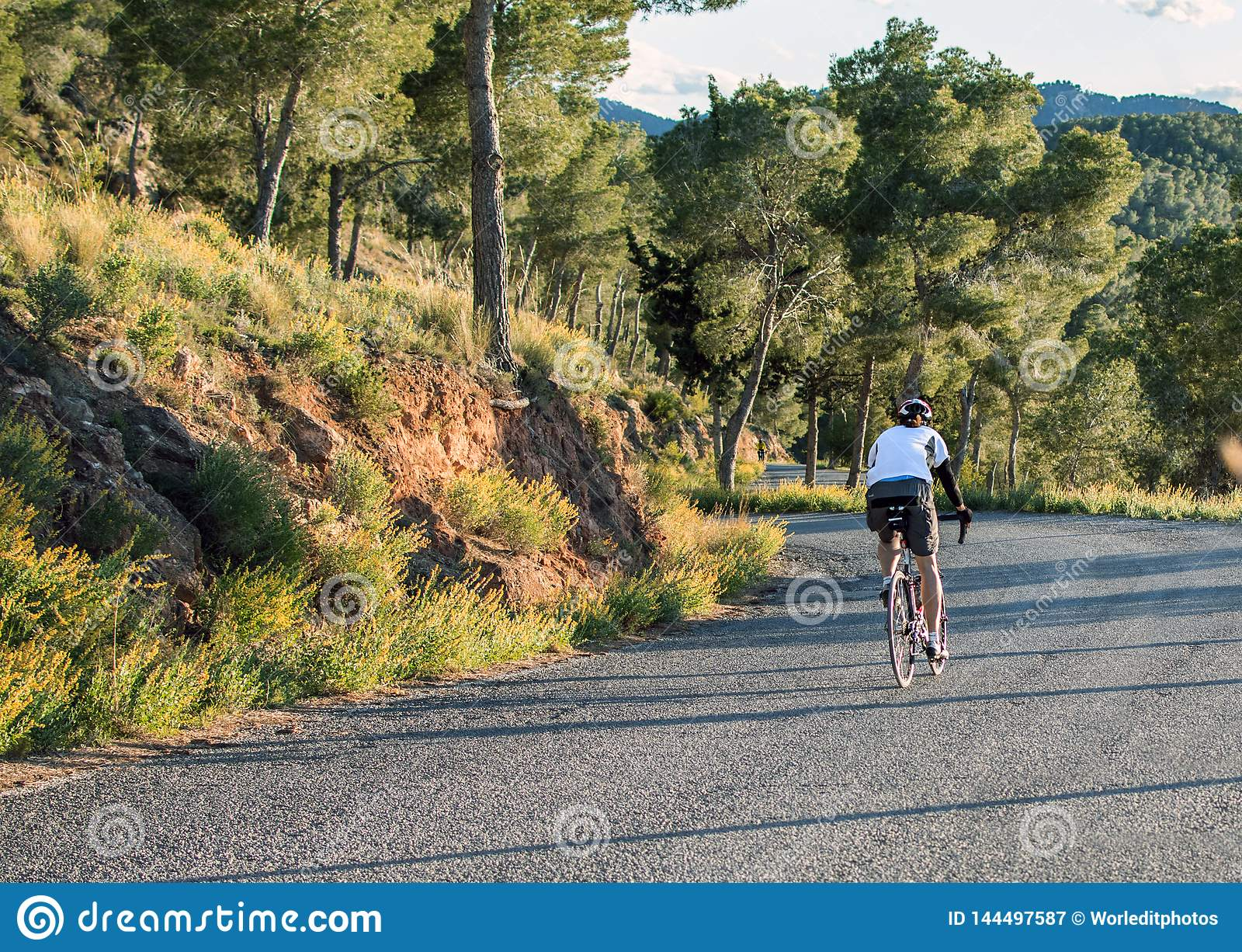 Murcia, Spain - April 9, 2019: Pro road cyclists enduring a difficult mountain ascent on his cool bicycle