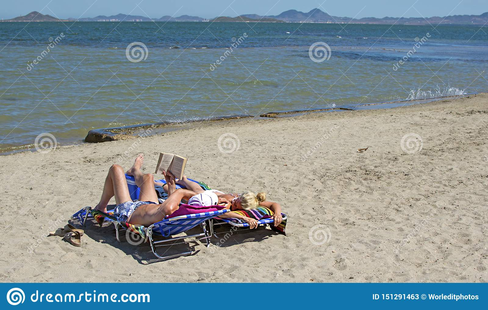 Murcia, Spanien - 22. Juni 2019: Glückliches Paar, das ein Buch liest und auf dem Strand während eines sonnigen Sommertages sich