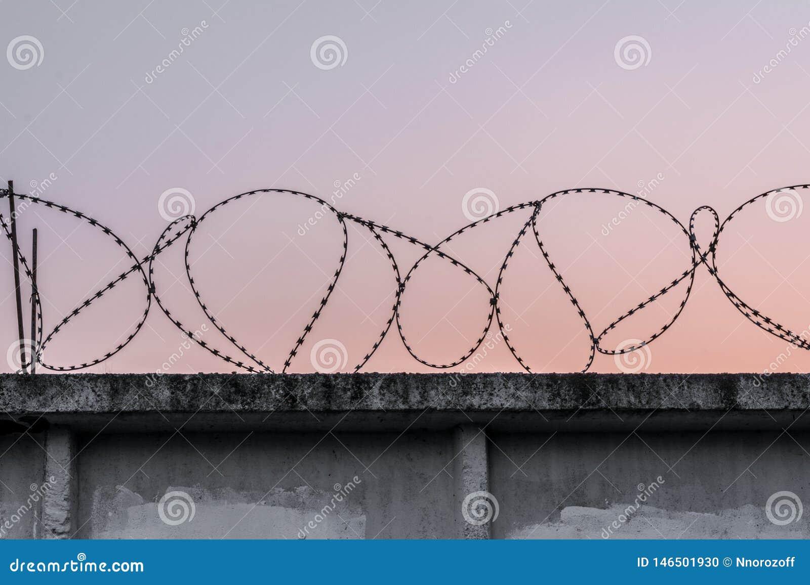 Muro de cemento con alambre de p?as contra un cielo de igualaci?n anaranjado azul