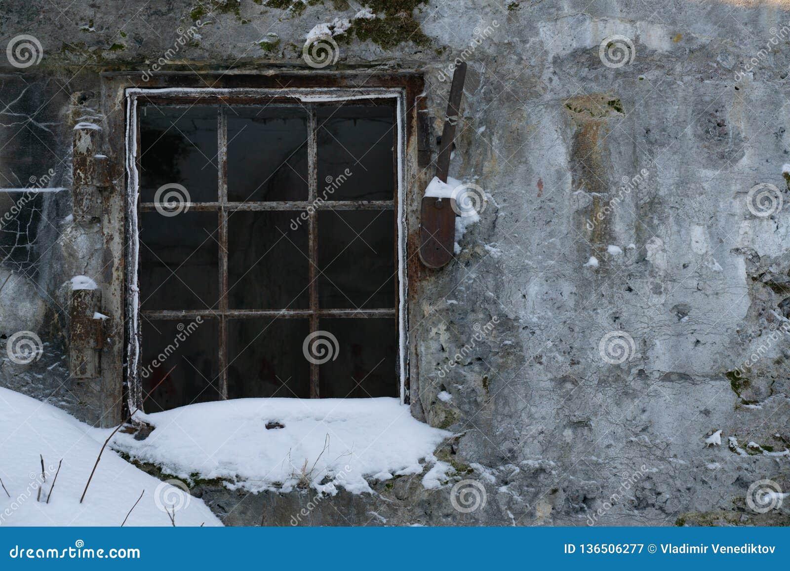 Muro de cemento y ventana viejos con la reja del metal