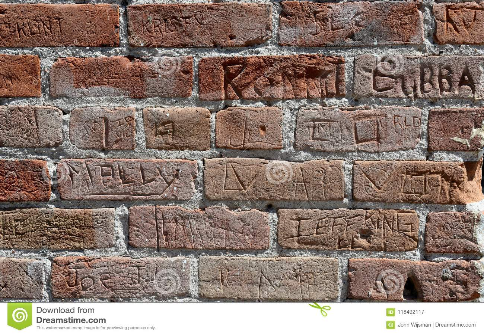 Muro di mattoni rosso con i nomi multipli cesellato nel mattone