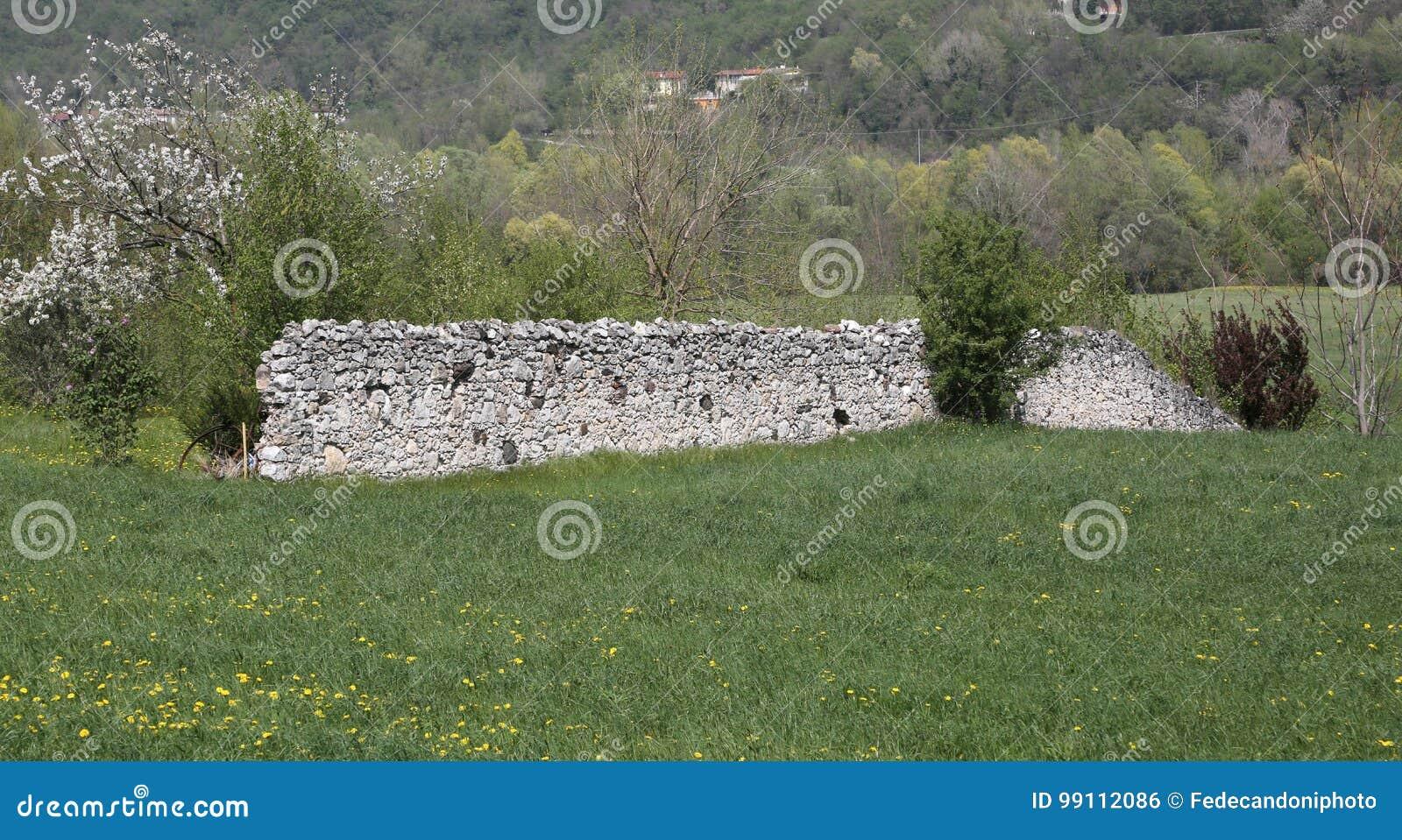 Muro Fatto In Pietra muro a secco fatto delle pietre in mezzo al prato fotografia