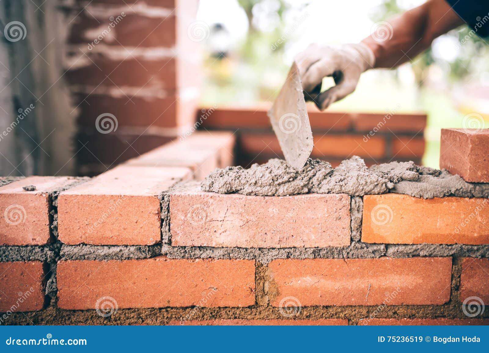 Murs de bâtiment de travailleur de maçon de construction avec le couteau de briques, de mortier et de mastic