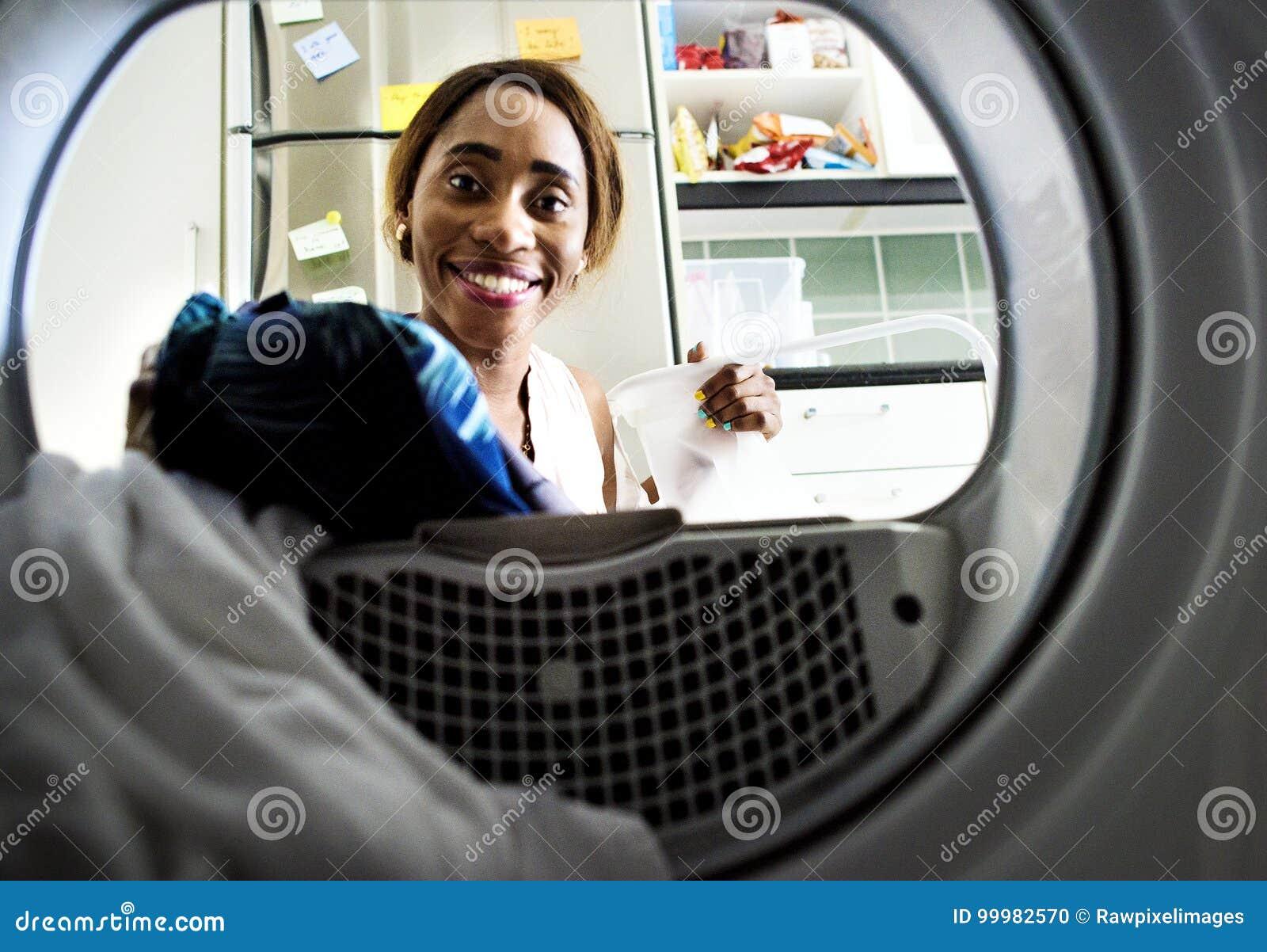Murzynka używa pralkę robi pralni