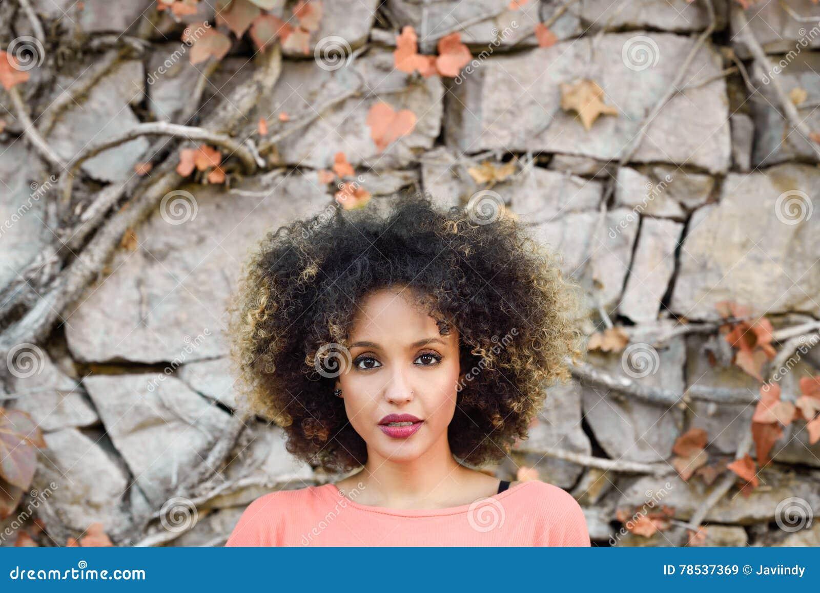 Murzynka z afro fryzury pozycją w miastowym parku