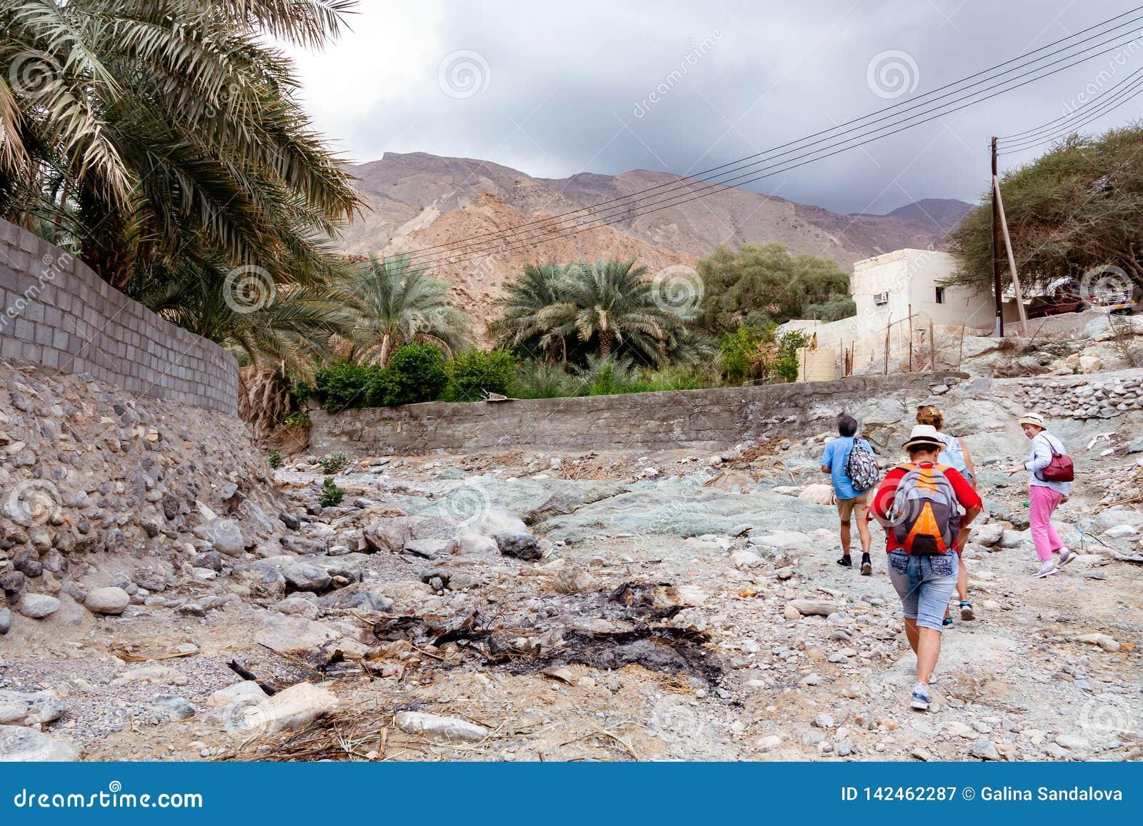 Muscat, Ομάν - 16 Δεκεμβρίου 2018: η ομάδα τουριστών περπατά κατά μήκος του wadi - μια στεγνωμένη κοίτη ποταμού - στα περίχωρα Mu