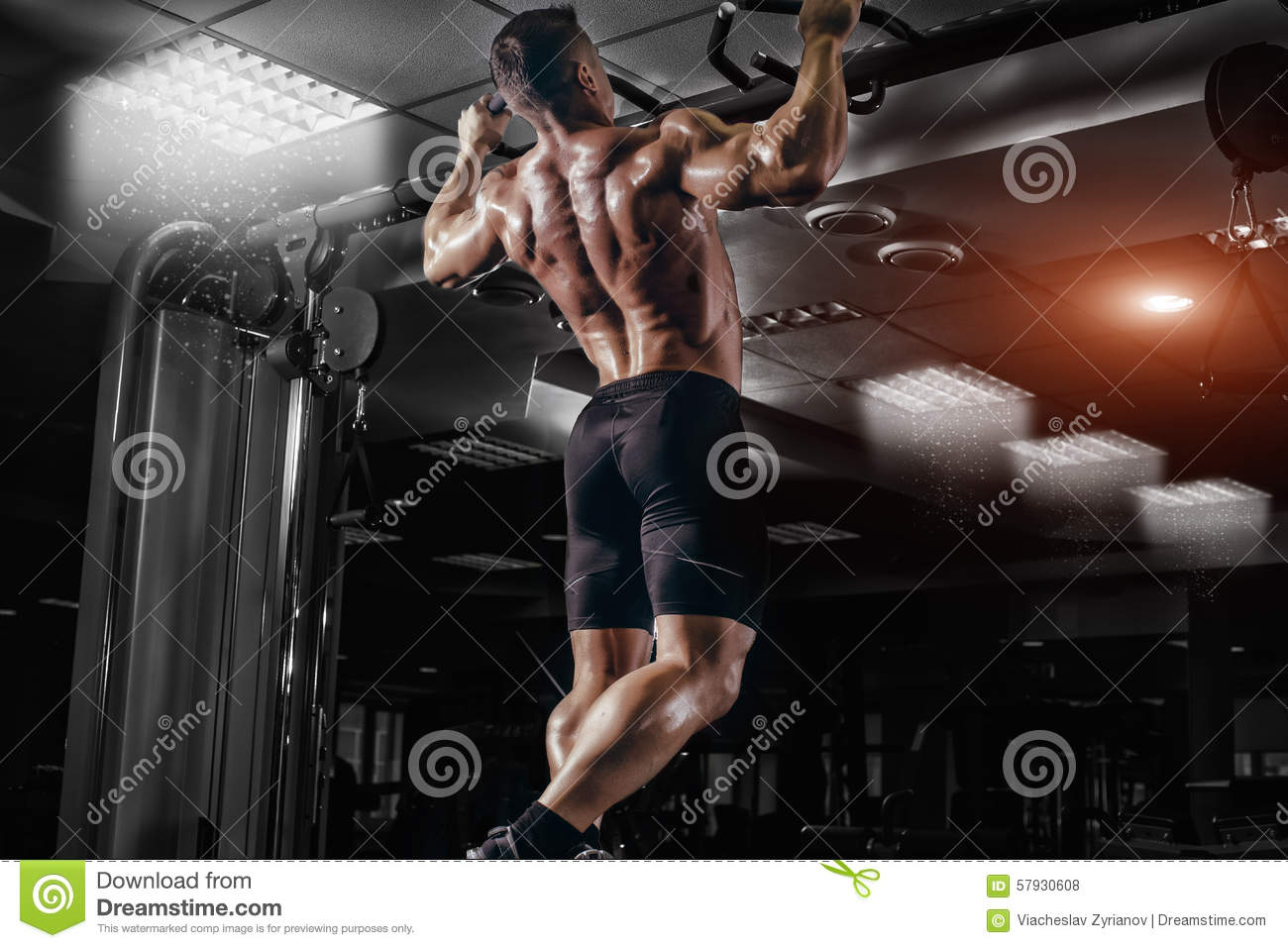 Muscle athlete man in gym making pull up