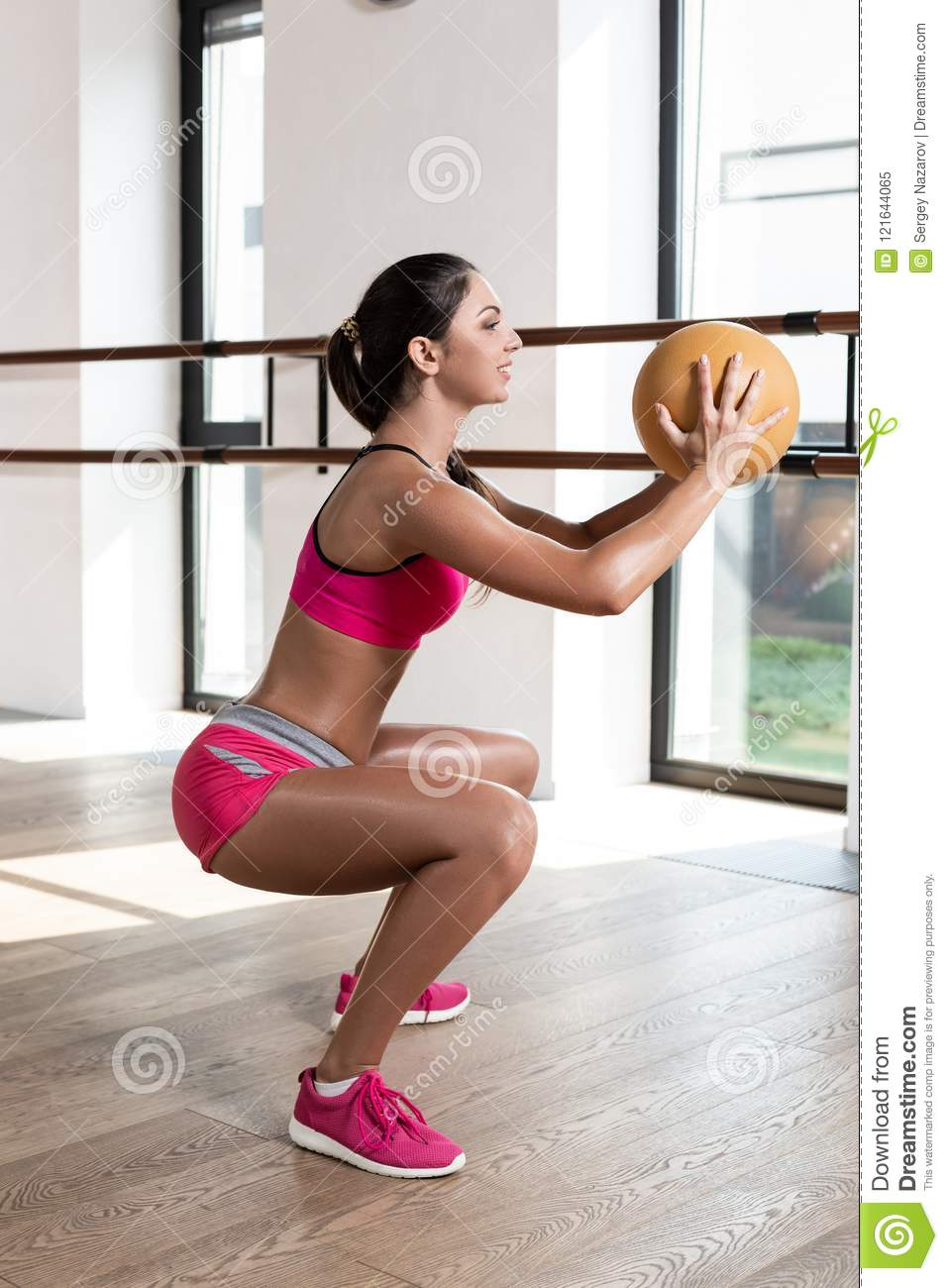 Strong Female Squatting On Fitness Mat With Weight Medicine Ball In