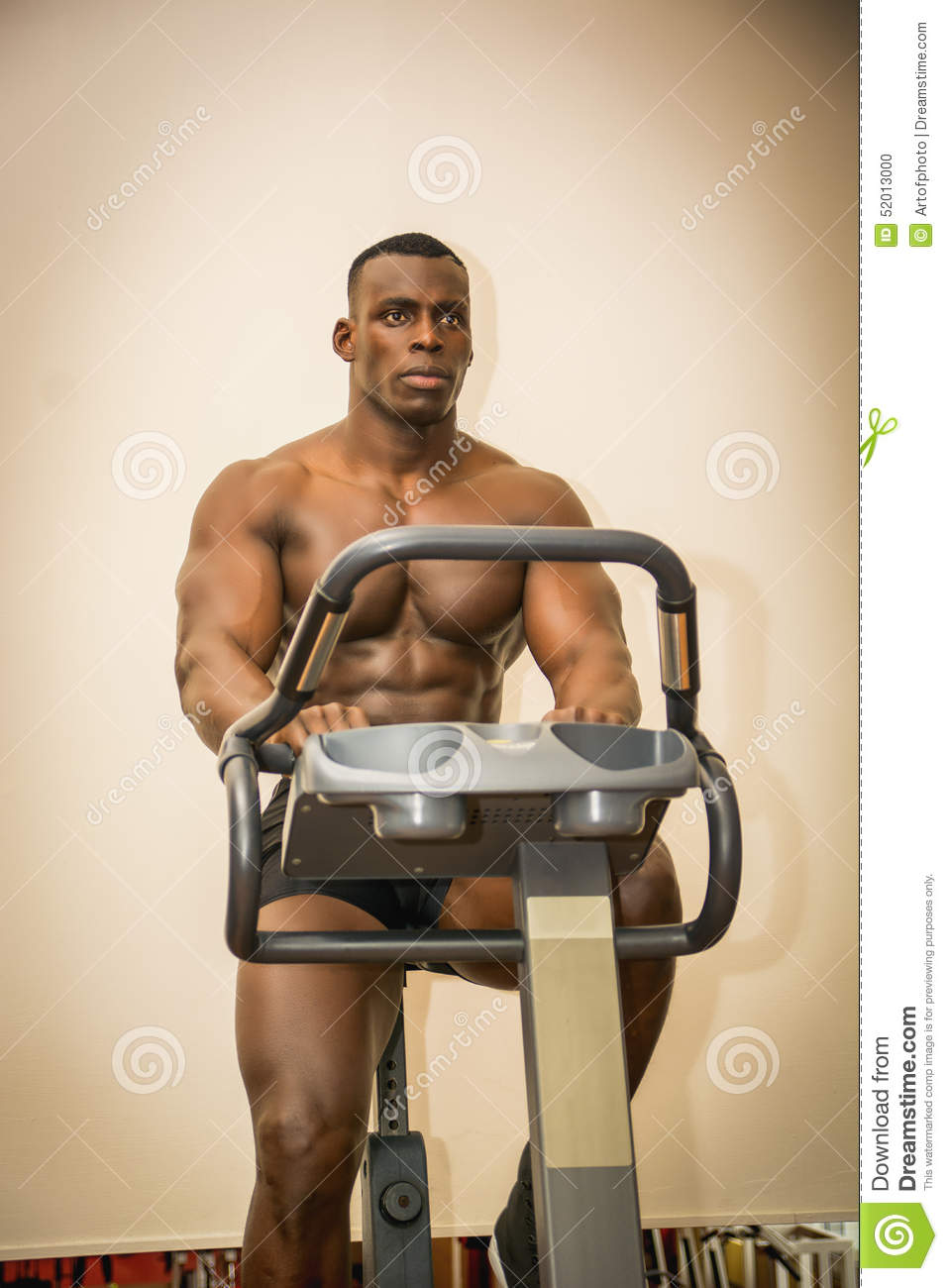Muscular Black Bodybuilder Exercising On Stationary Bike In Gym