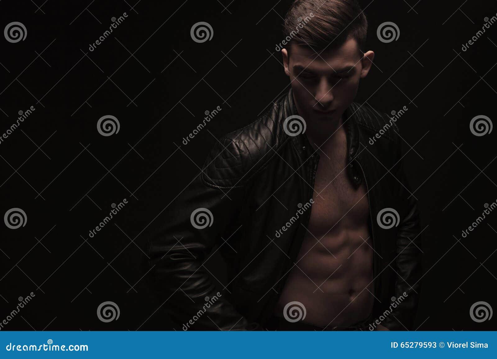 Muscular boy posing shirtless in studio background while wearing