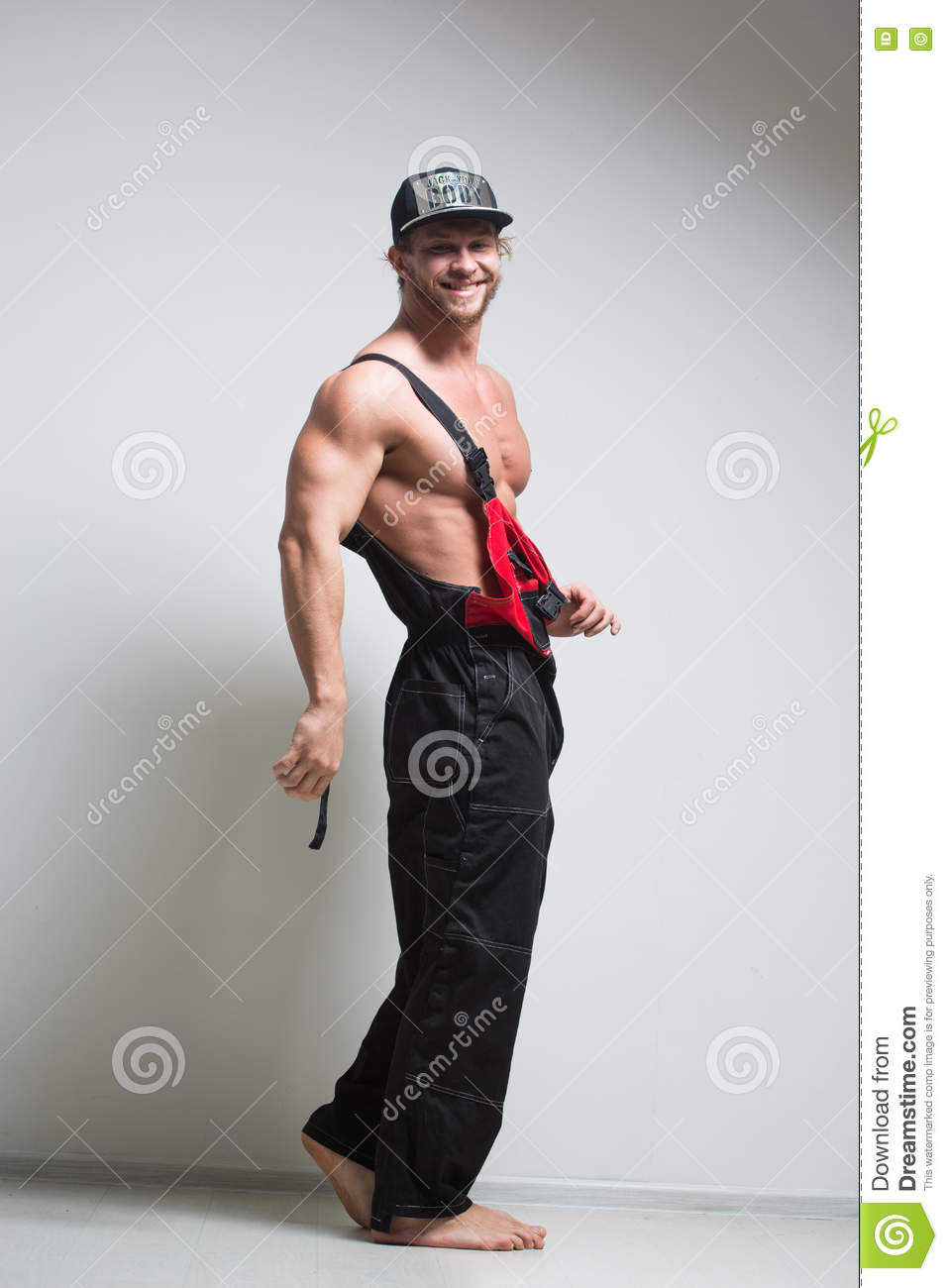 Muscular Construction Worker In Overalls Stock Photo