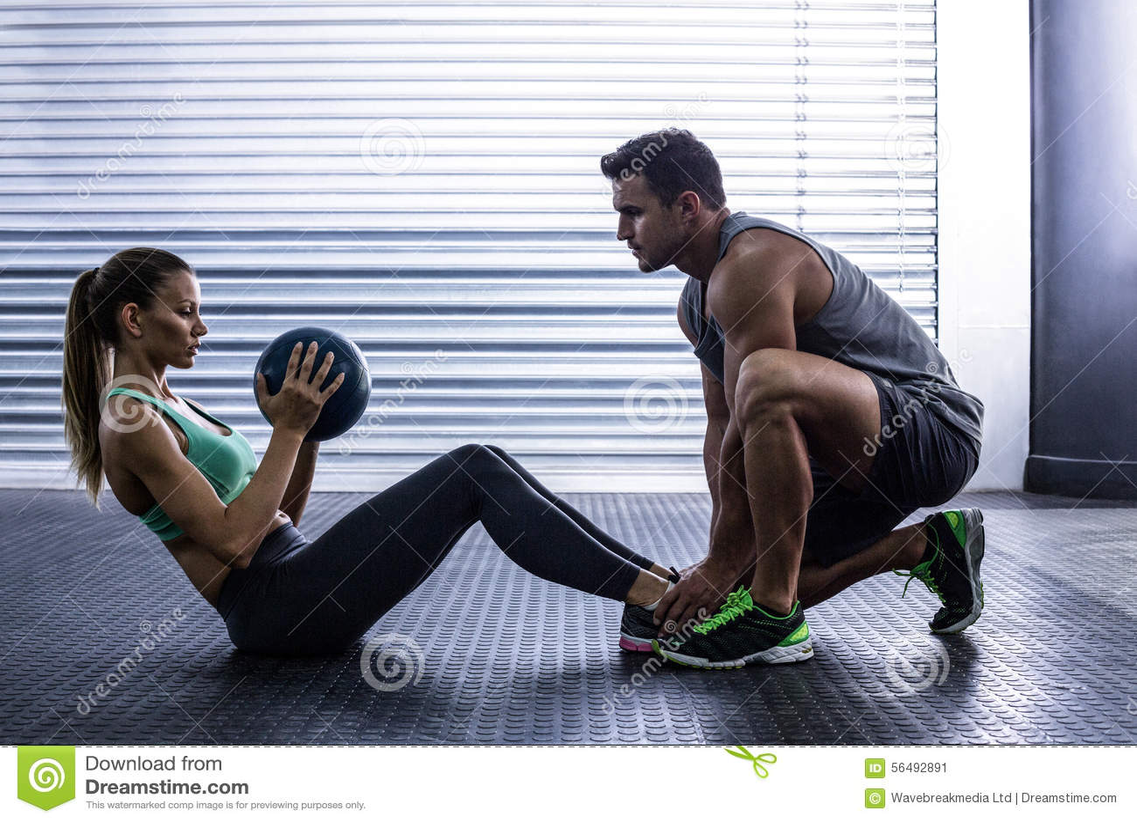 Muscular couple doing abdominal ball exercise