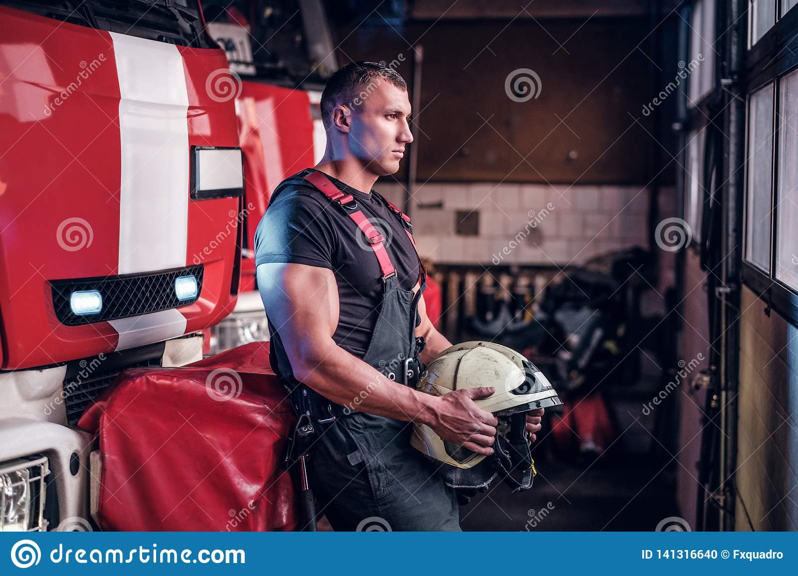 Muscular fireman holding a protective helmet in a garage of a fire department