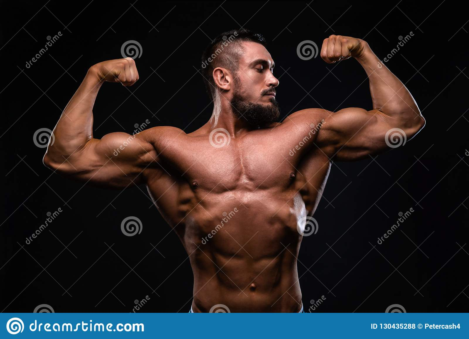 Muscular fitness burnet beard man is showing biceps on black background