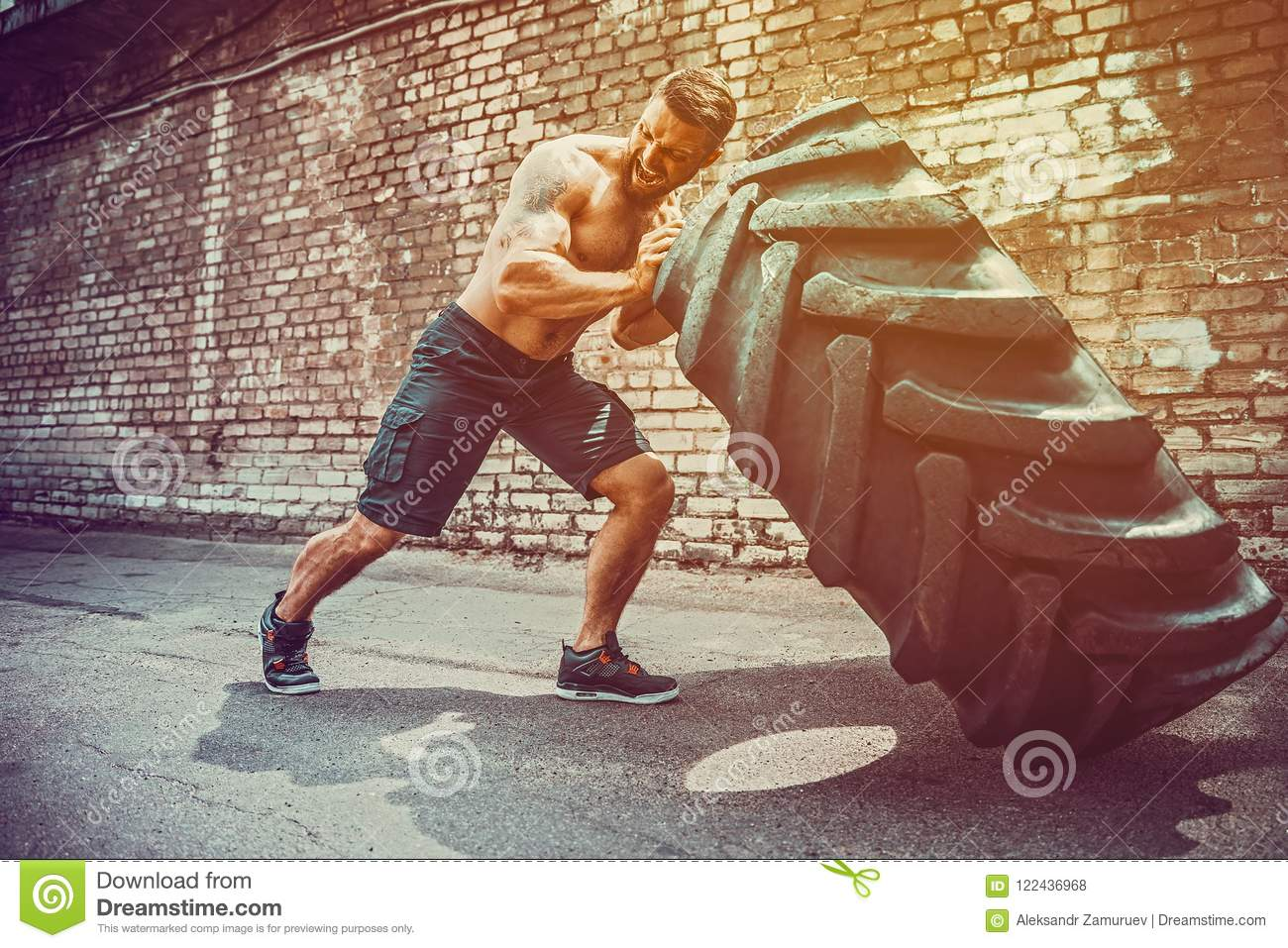 Muscular fitness shirtless man moving large tire in gym center, concept lifting, workout cross fit training