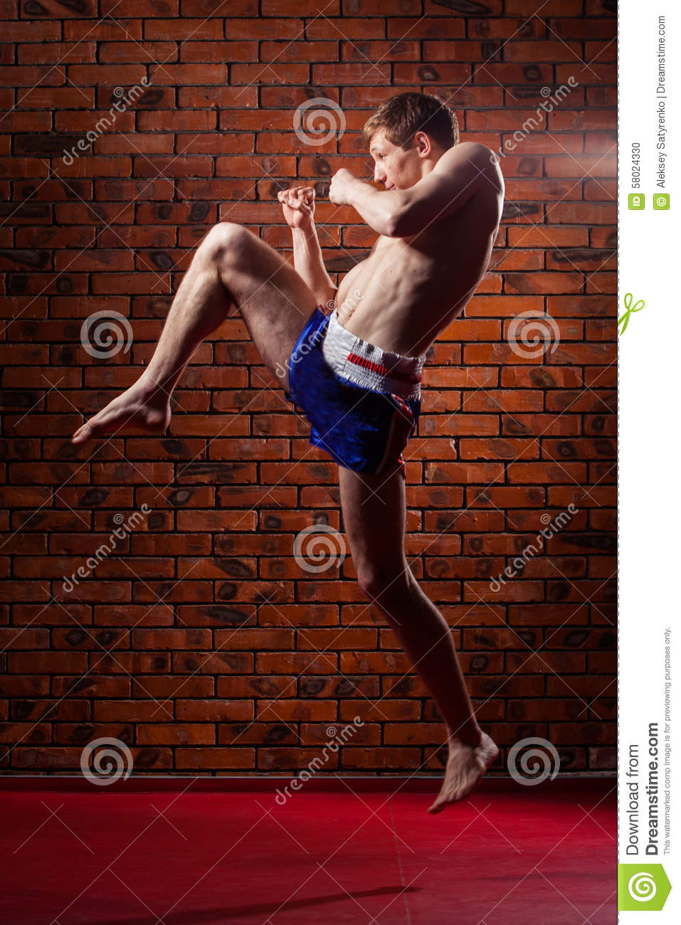 Muscular handsome fighter giving a forceful