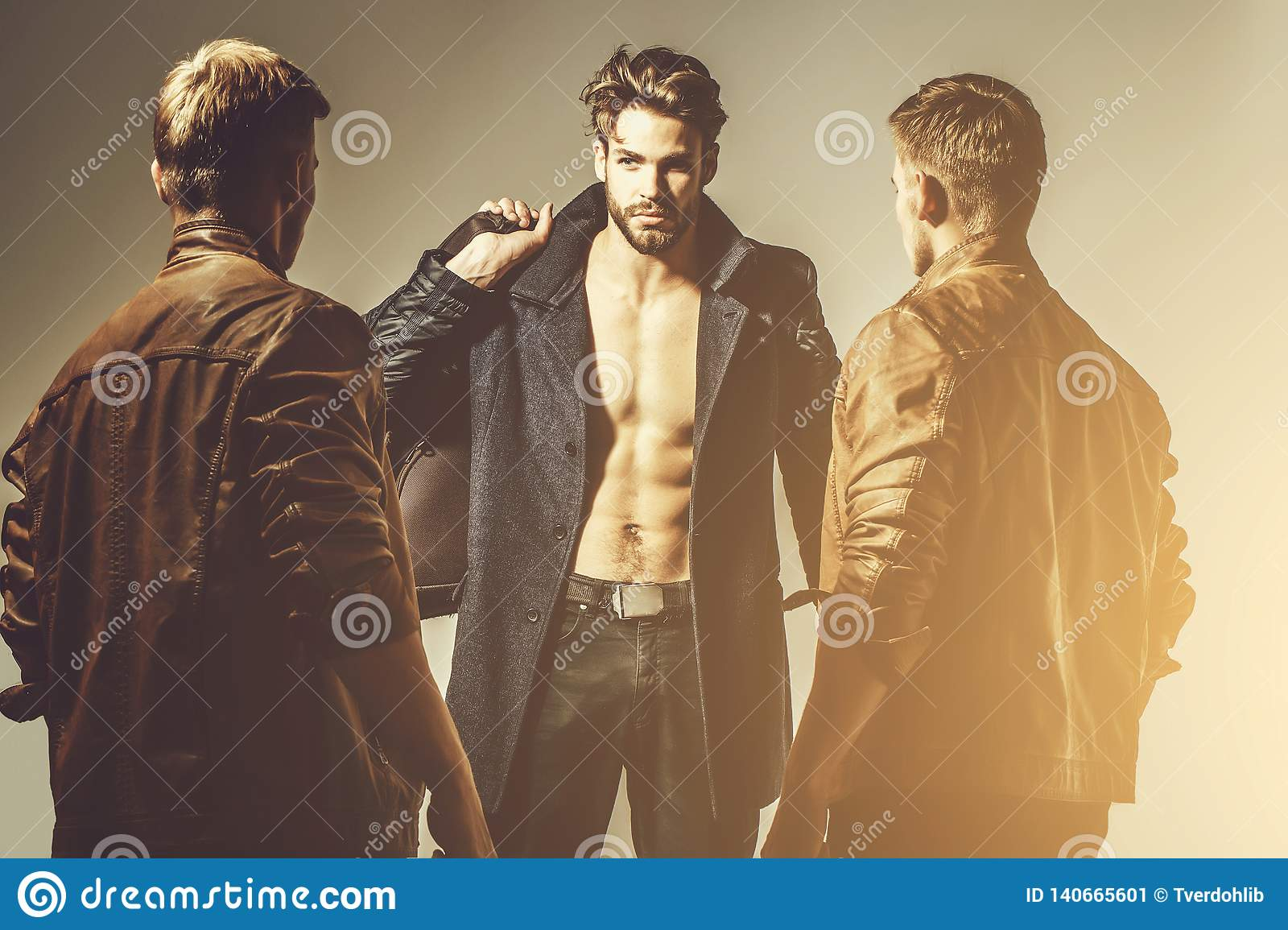 Three handsome muscular men or bearded macho guys with naked torso and body  holds bags, suitcase in fashionable brown leather jacket, coat and pants on  grey ...