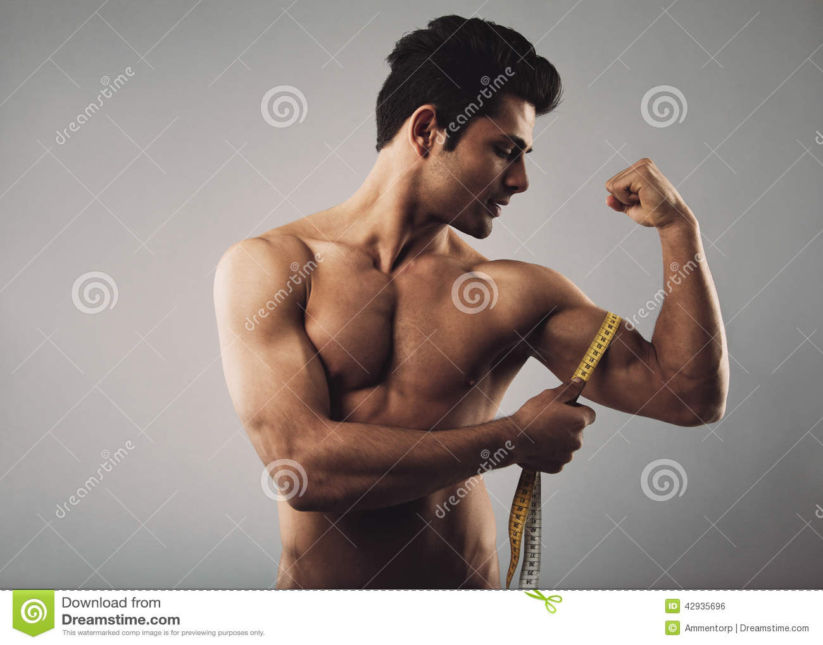 Muscular male measuring biceps