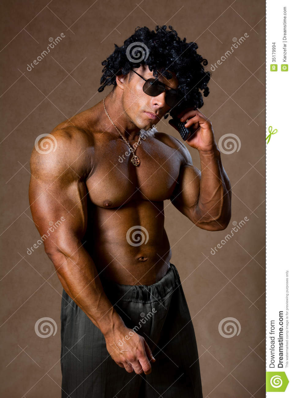 Muscular Man With Curly Hair Talking On A Cell Phone