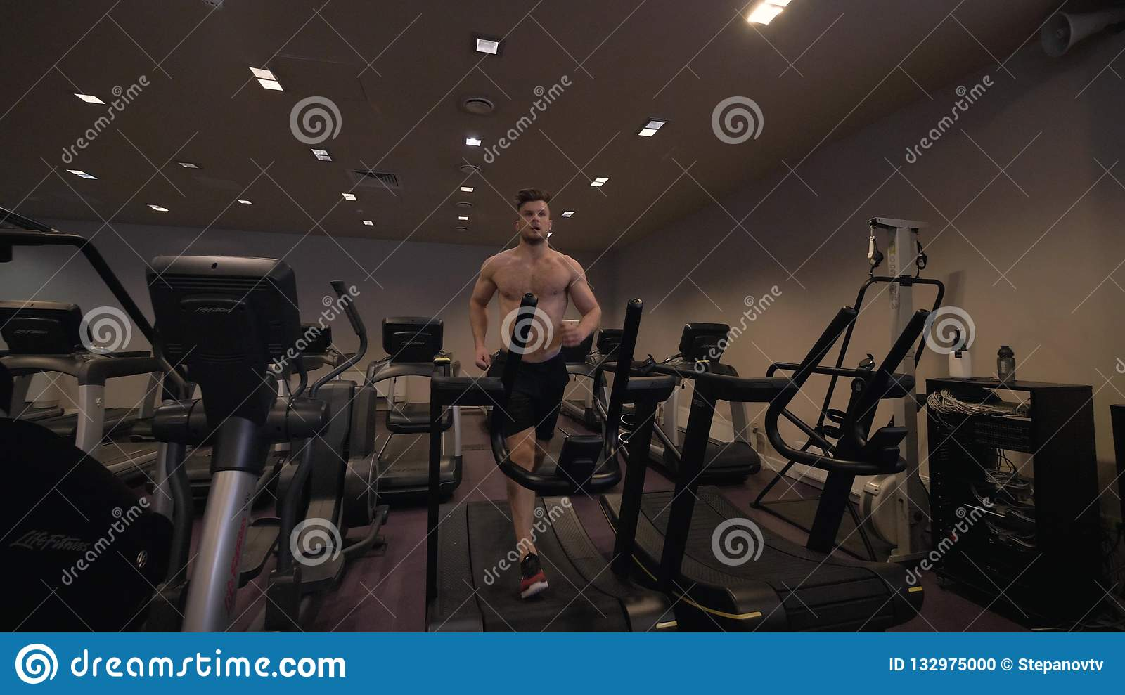 Muscular man doing cardio training on treadmill in healthy club slow motion
