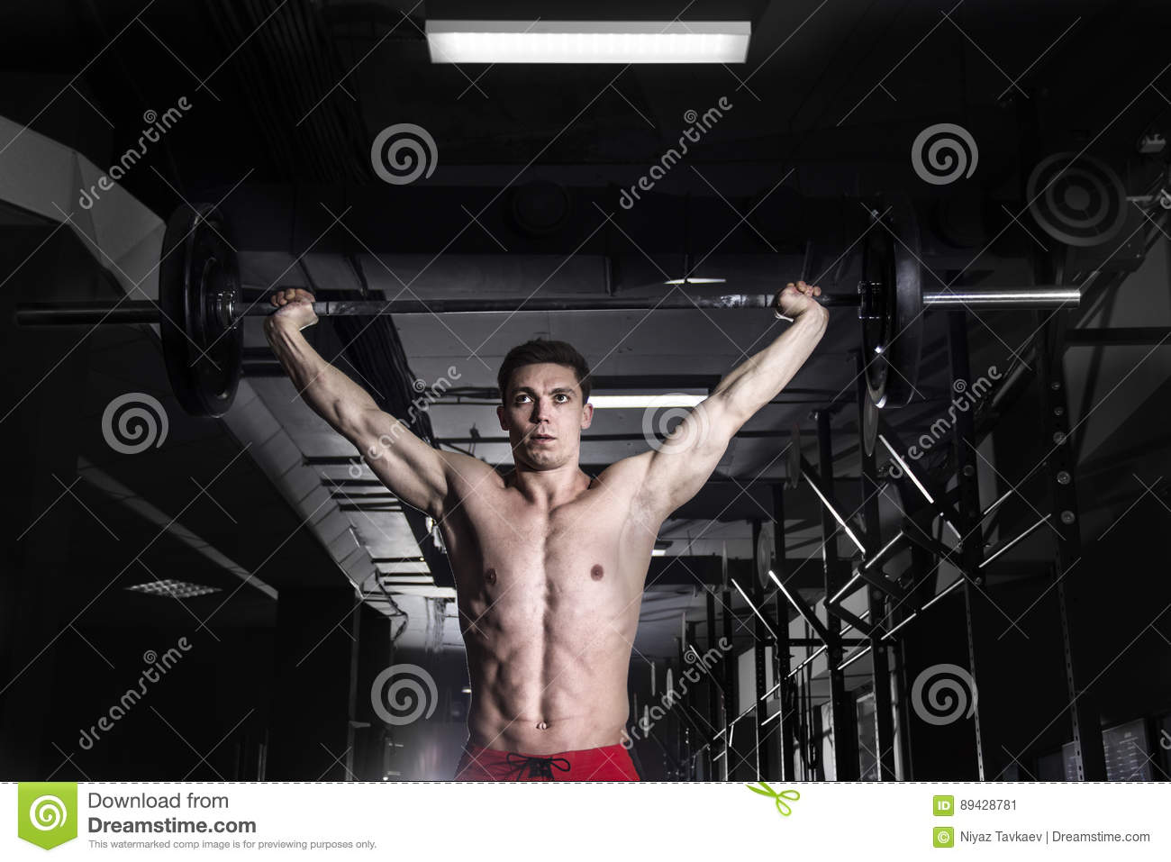 Muscular man doing the crossfit exercise in the gym.Crossfit wit