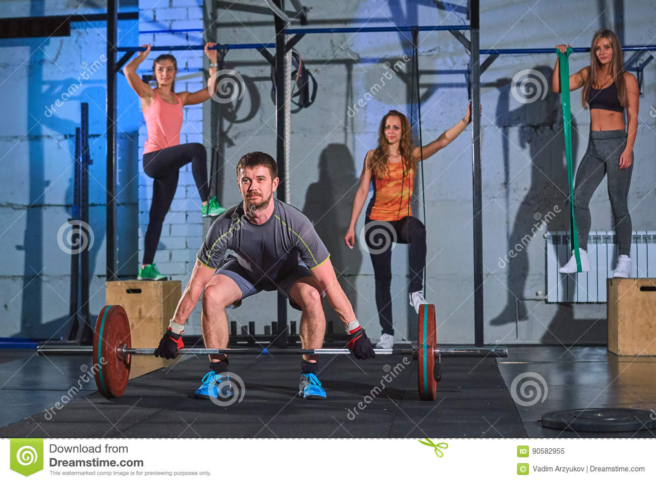 Muscular man doing squats with barbell in a gym, Beautiful girls in the background