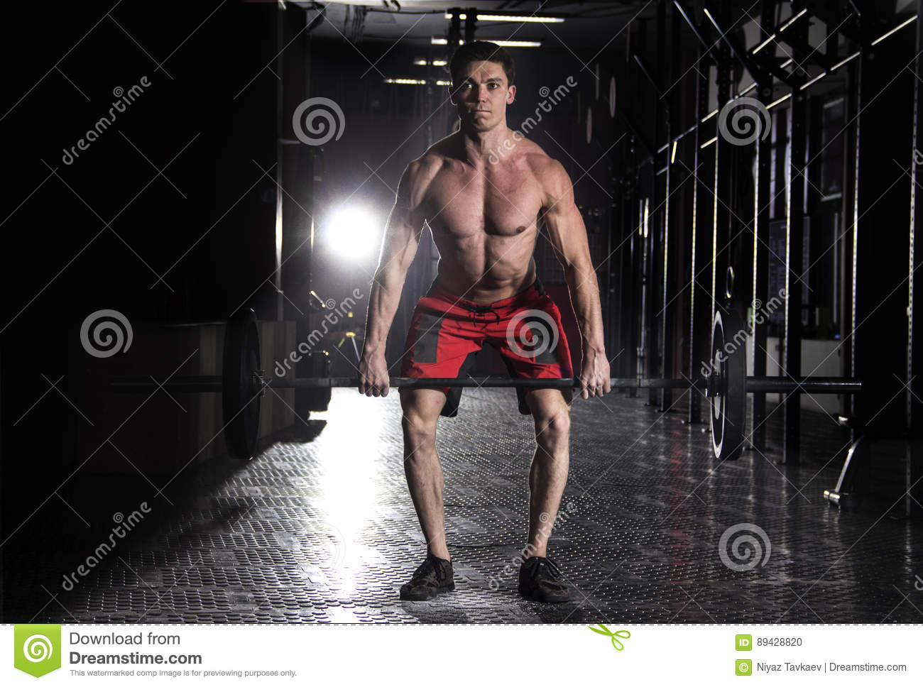 Muscular man lifting a barbell in crossfit gym.