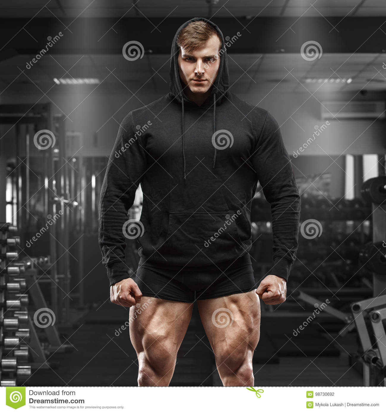 Download Muscular Man With Muscle Legs In Gym. Strong Male In Black Hoodie With Big Quads Stock Photo - Image of posing, muscle: 98730692