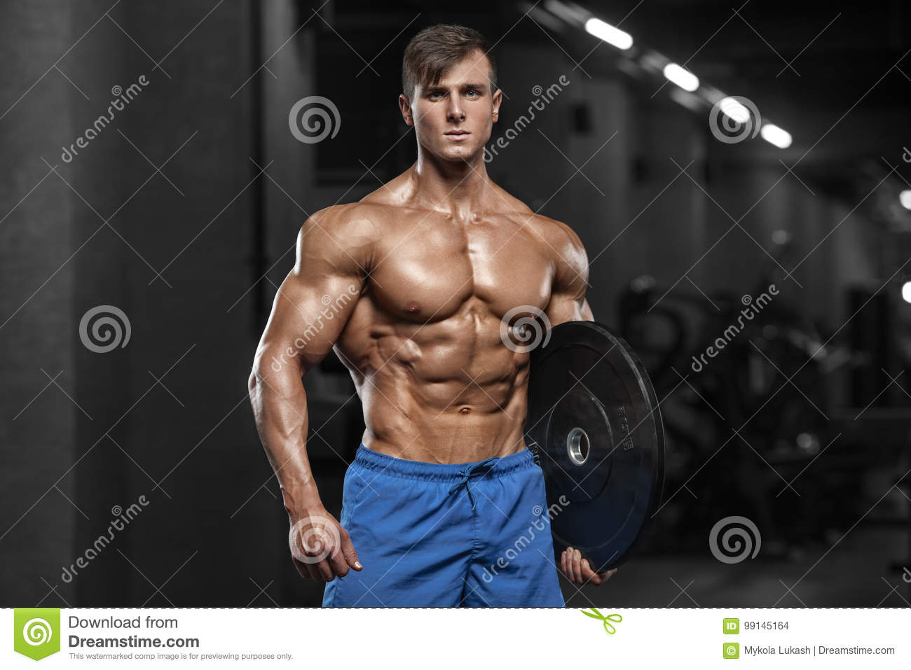Muscular man showing muscles, posing in gym. Strong male naked torso abs,  working out.