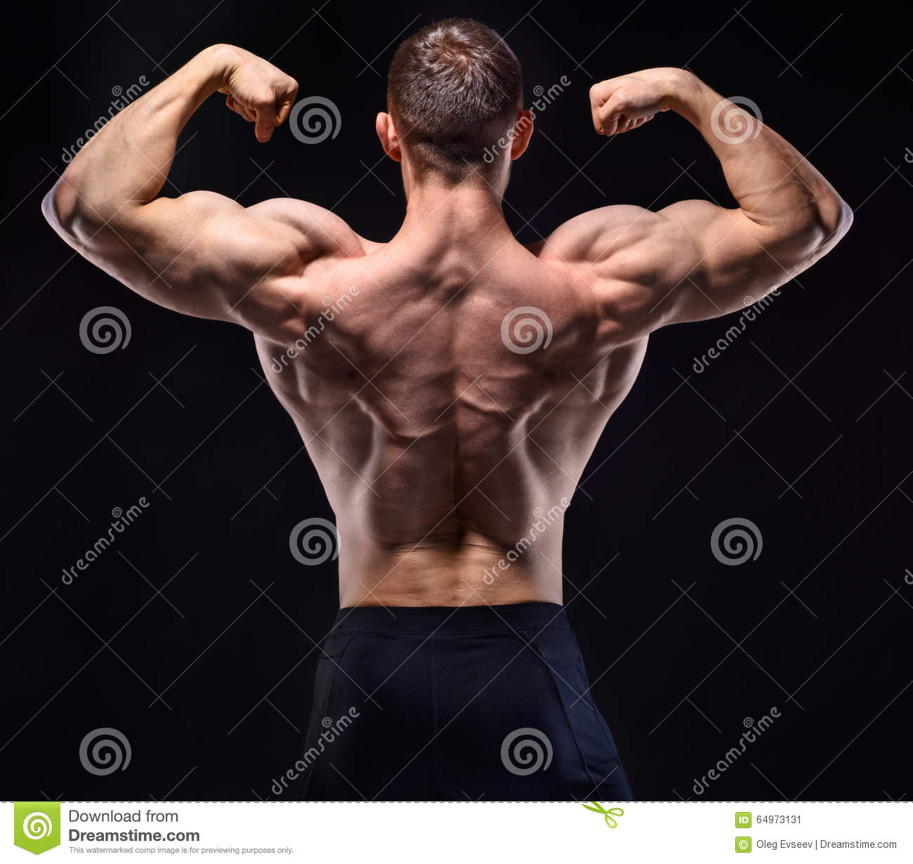 Muscular man in studio show his back