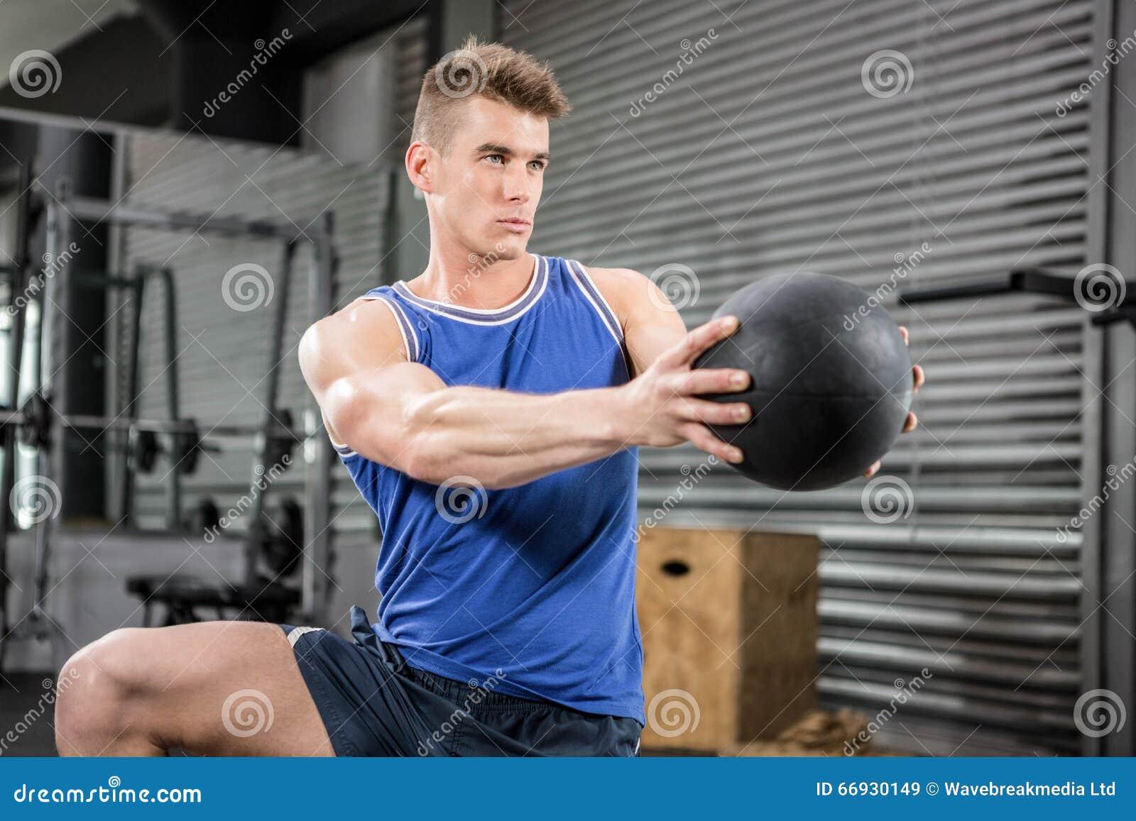 Muscular man training with medicine ball