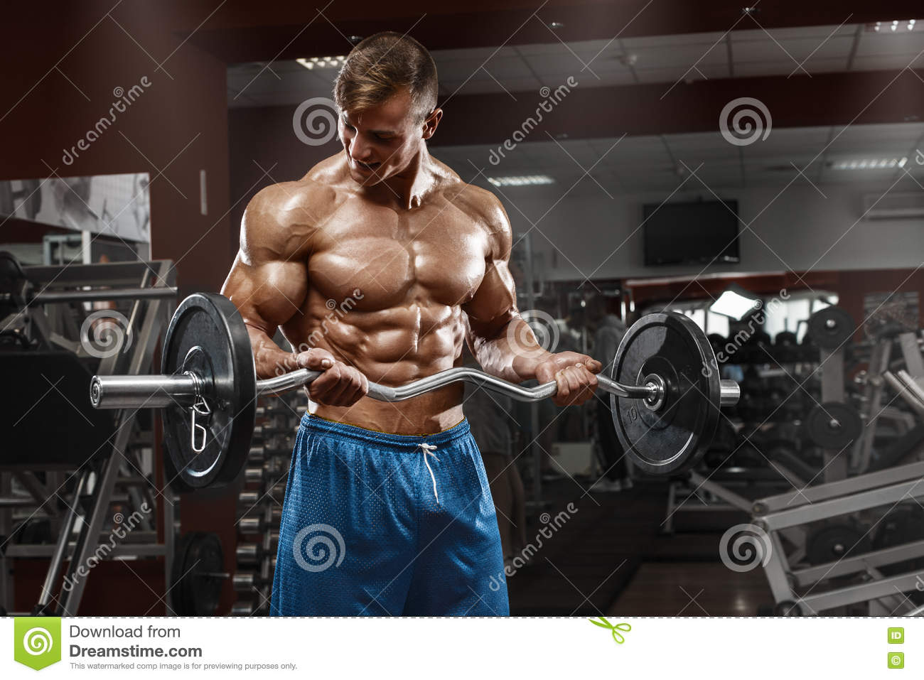 Muscular man working out in gym doing exercises with barbell at biceps, male naked torso abs