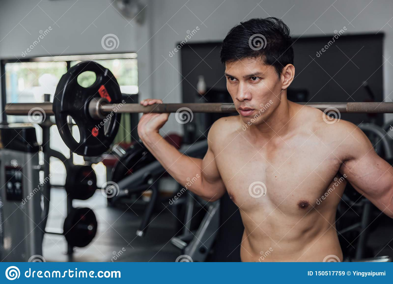 Muscular Man Working Out In Gym Doing Exercises Stock