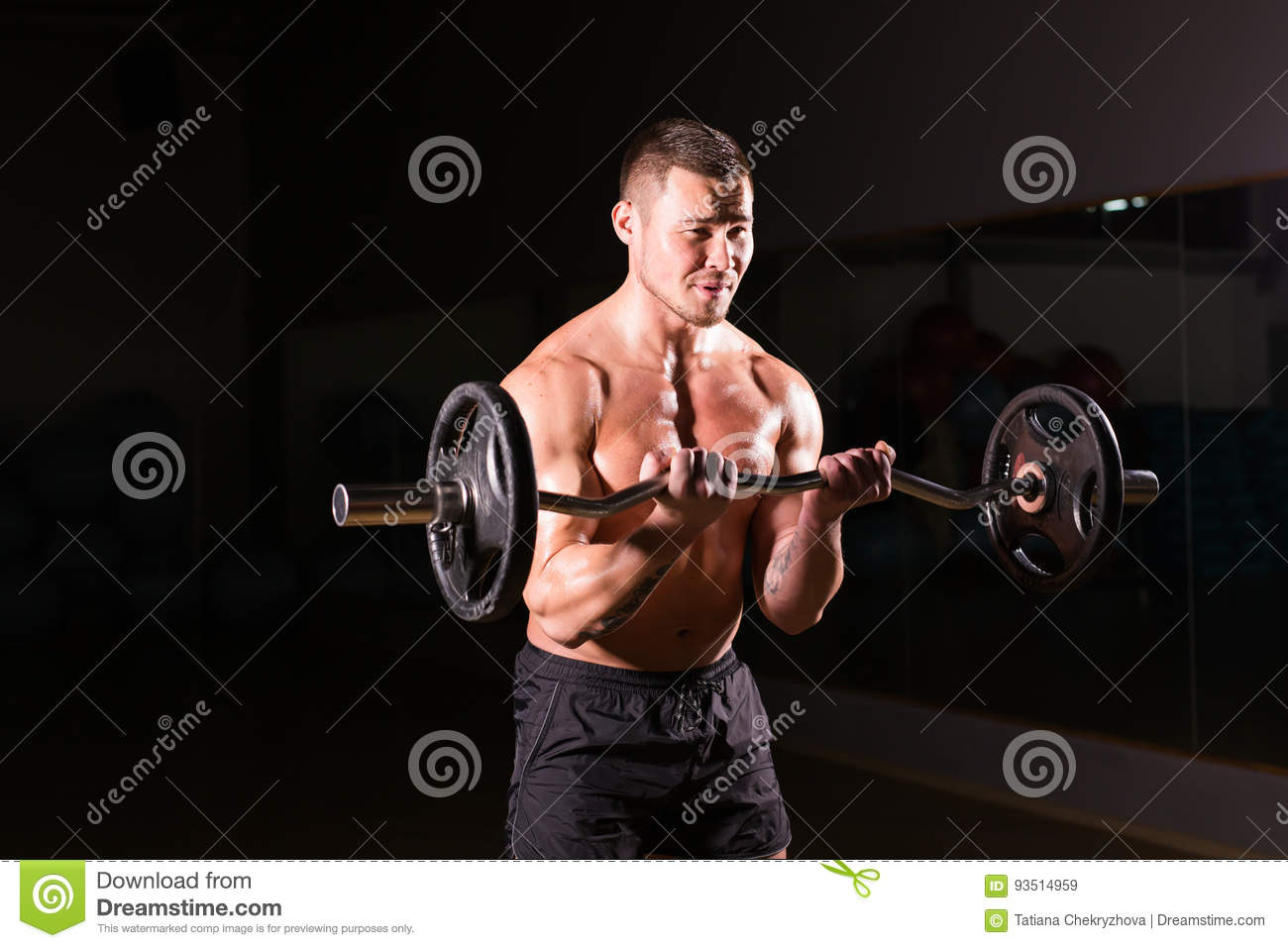 Muscular man working out in gym doing exercises with barbell, strong male naked torso abs.