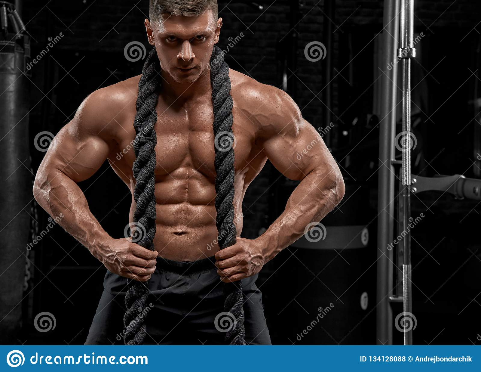 Muscular man working out in gym doing exercises