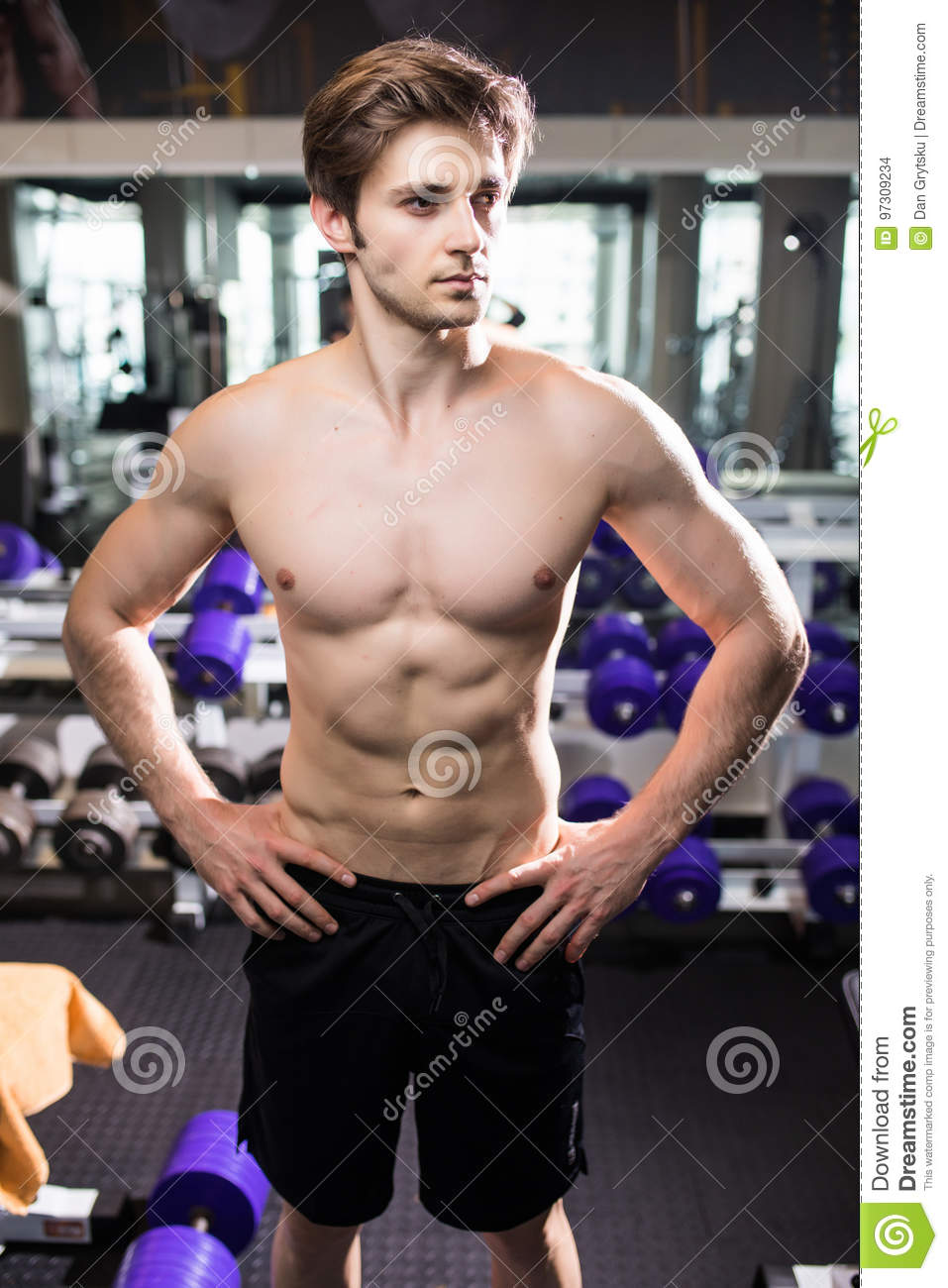 Muscular man working out in gym doing exercises at triceps, strong male naked torso abs. Fitness
