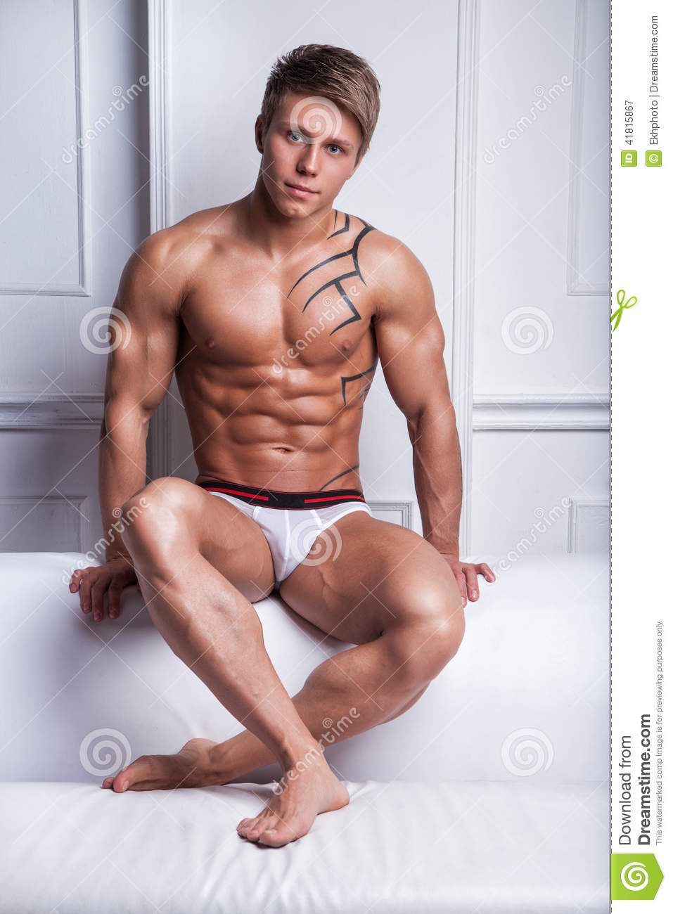 Naked guy sitting on a sofa