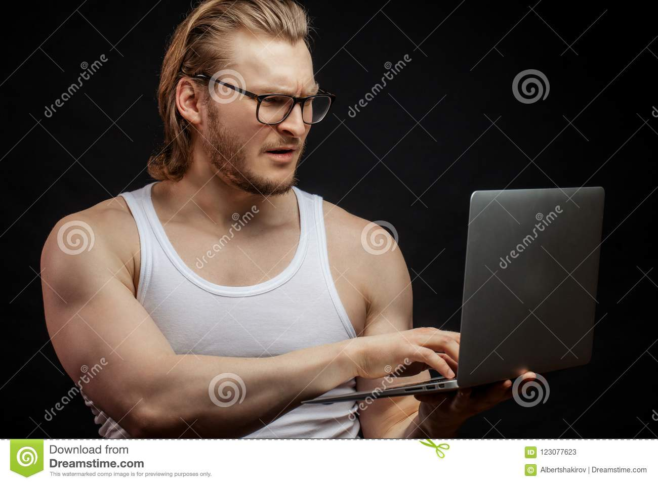 Muscular athlet learning to work with computer