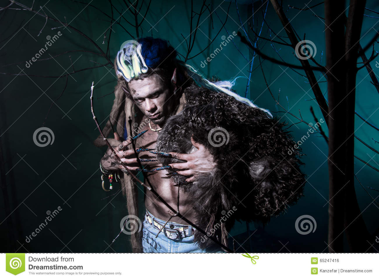 Muscular werewolf with dreadlocks with long nails among the bran