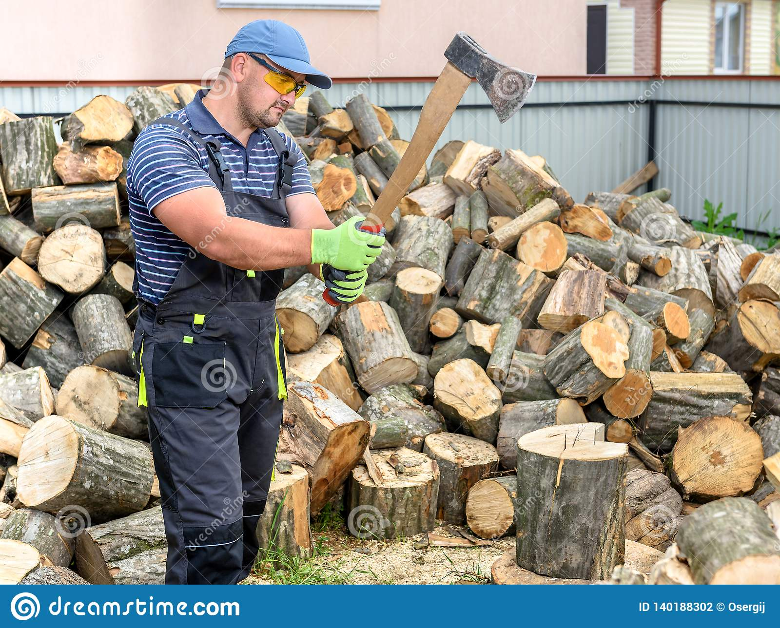 Man Splitting Wood And Cutting Firewood With Axe Stock ...