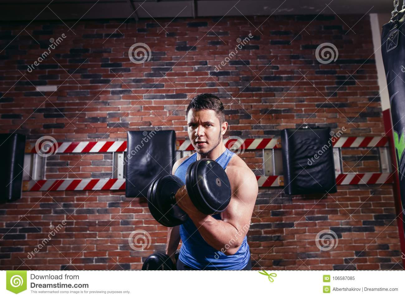 Strong Athletic Man With Dumbbell Showes Muscular Body