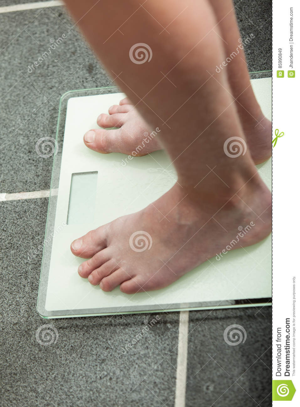 Muscular young man weighing himself on a scale