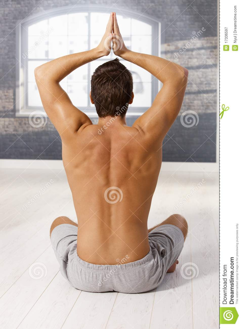 Muscular young man in yoga exercise