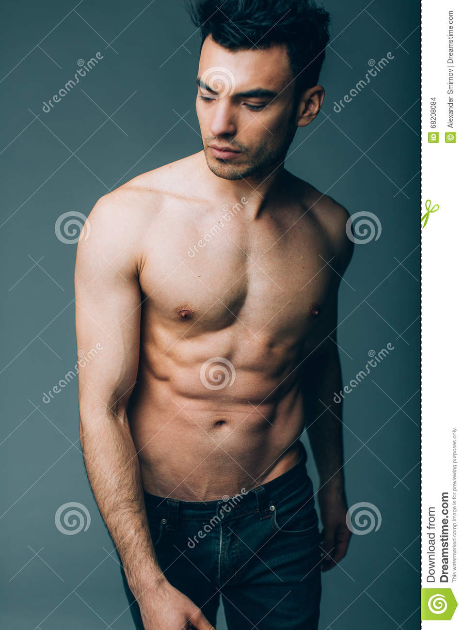 Muscular Young Guy Posing In Studio In Jeans Stock Image