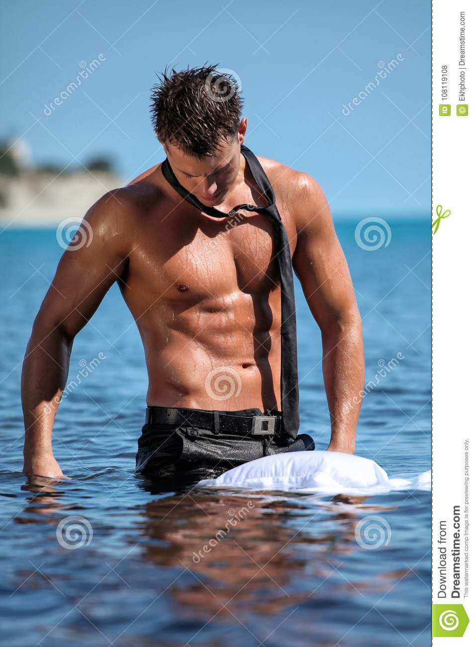 7dea3c6855 Muscular young wet guy standing in the sea takes off his business suit with  a tie outdoors