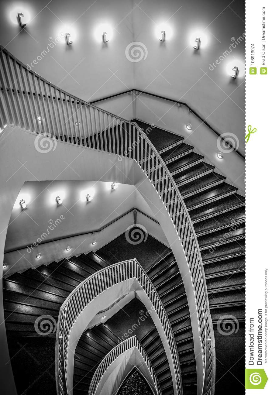 Looking Down Spiral Staircase With Wall Sconces Lighting The Way Indoors