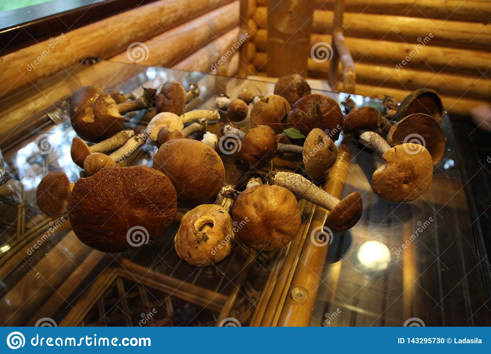 Mushrooms lie on a glass table in a wooden house